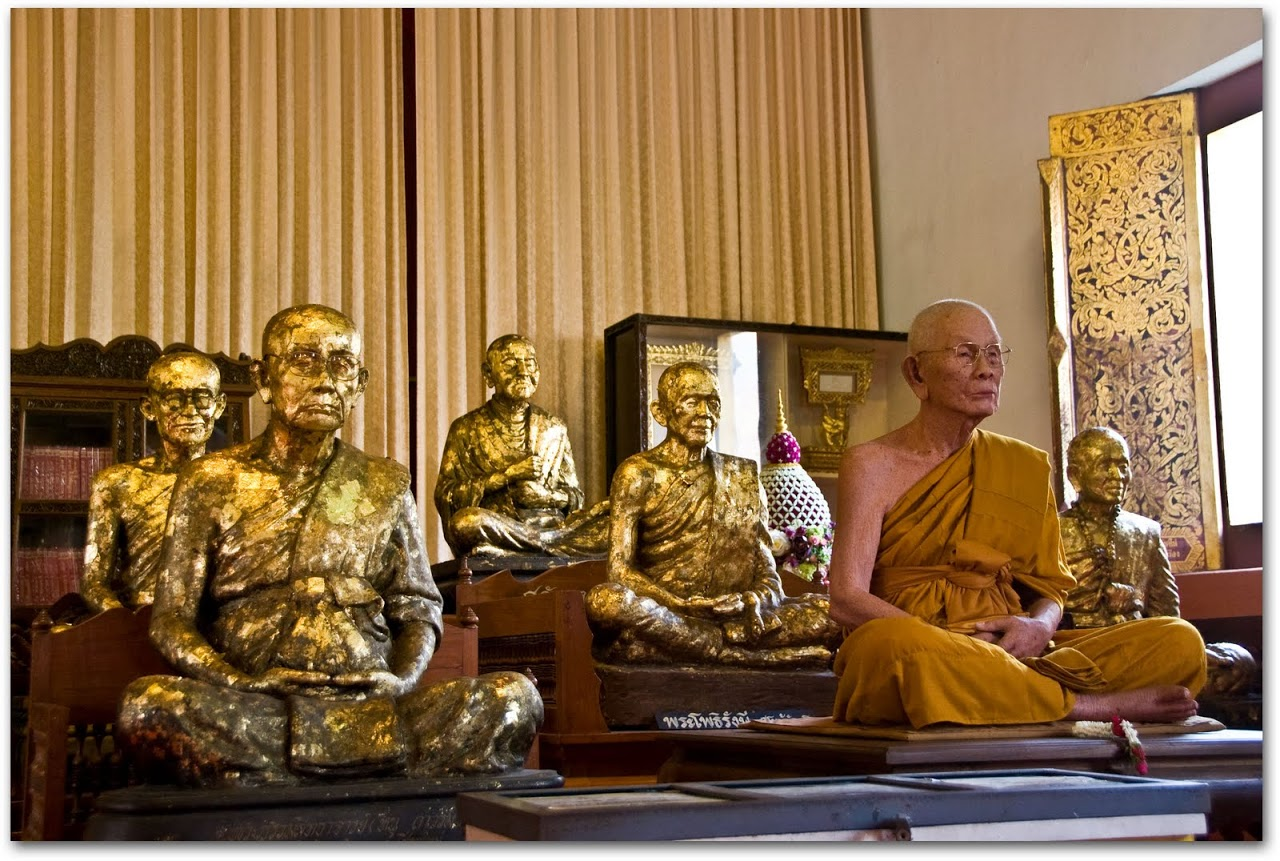 Monk sitting amidst golden monks